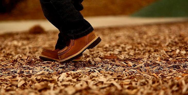 man walking on wood chips
