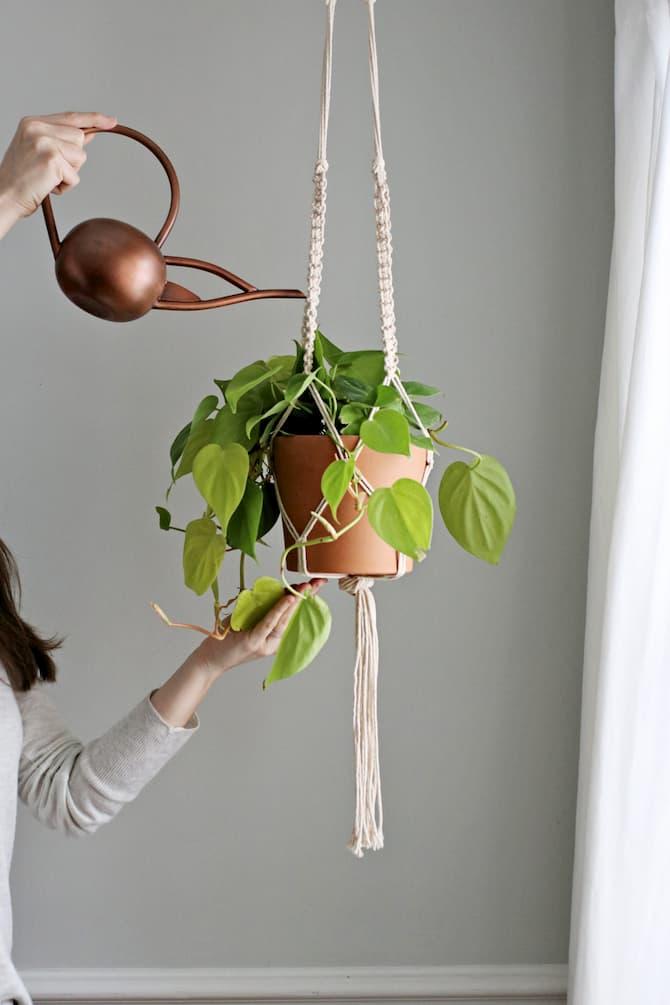 woman watering macrame plant