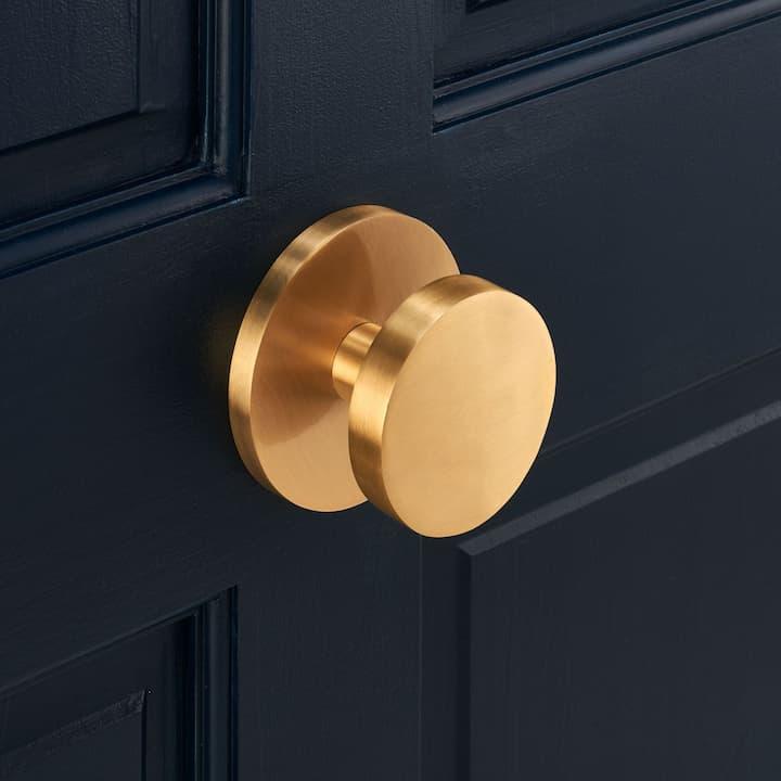 modern gold door knob on black door
