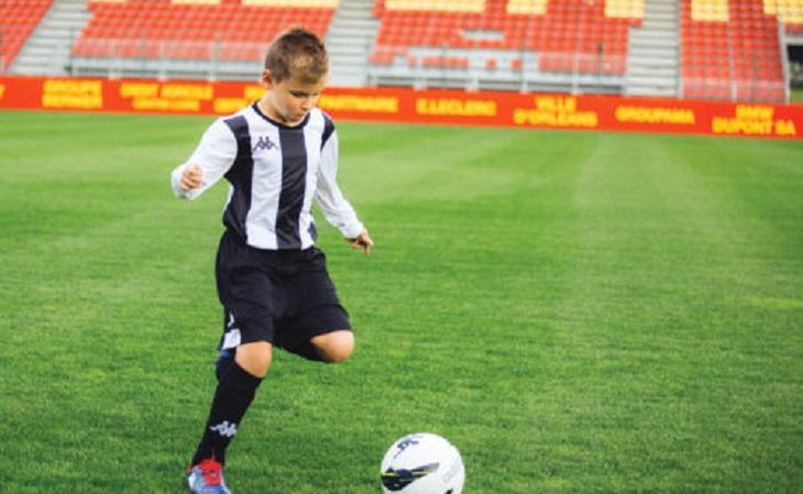 kid wearing kappa jersey on grass and playing football