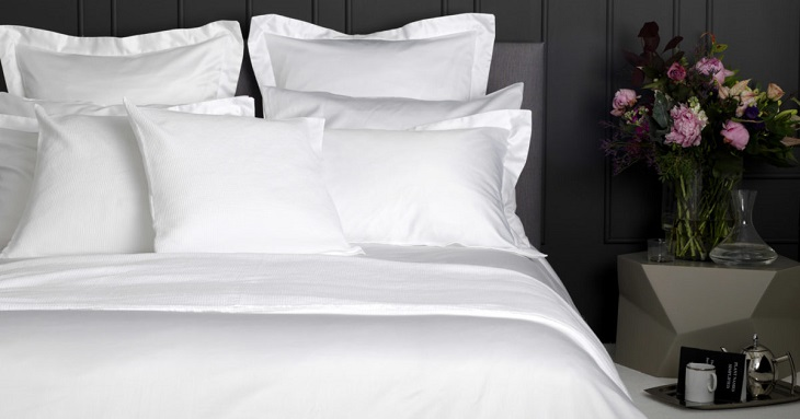 white bed sheets with flowers on nightstand