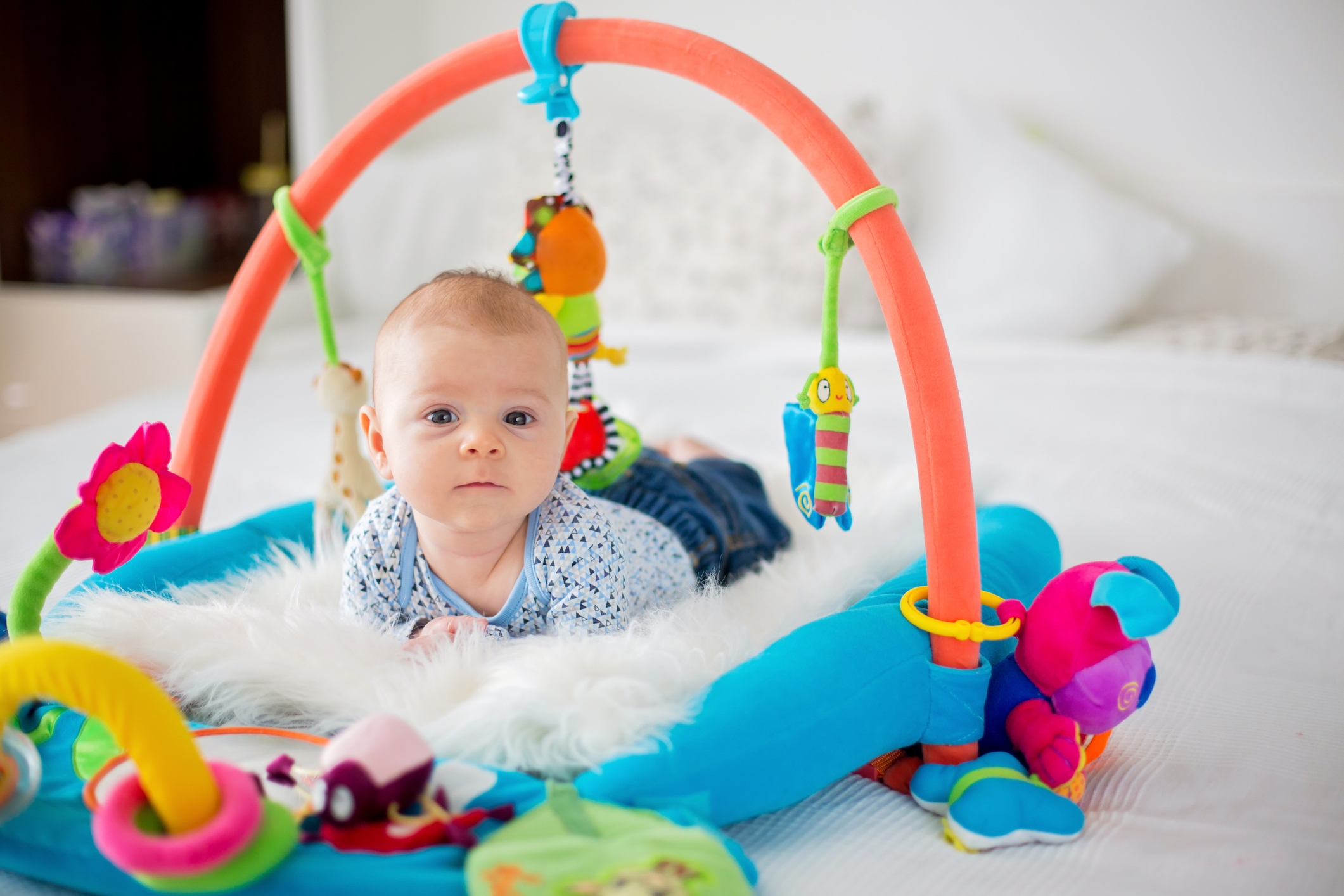 Cute baby boy on colorful gym, playing with hanging toys at home